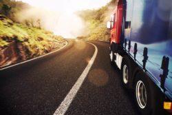Transport międzynarodowy. Ciężarówka jadąca drogą lokalną w stronę słońca.