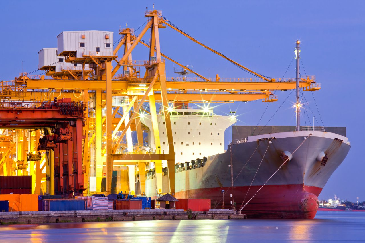 Transport międzynarodowy. Statek towarowy ładowany z nabrzeża.