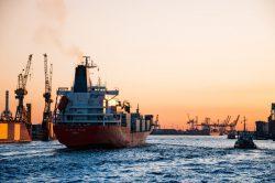 Import z Chin Kontenerowiec wpływający do portu w Hamburgu o zachodzie słońca