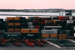 Import z Chin. Spiętrzone kontenery czekające w magazynie na załadunek na statek towarowy.