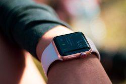 Import z Chin. Mężczyzna sprawdza godzinę i powiadomienia na złotym smart watchu.