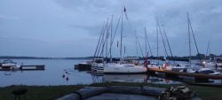 Żagle BBA 2020 - cisza na jeziorze po zakończeniu piątkowego ogniska. Jachty stoją zacumowane do pomostów, woda jest gładka z barkuwiatru.