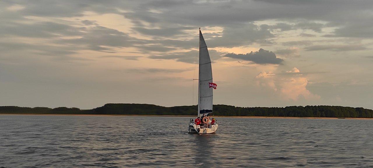 Żagle BBA 2020 - jacht pod banderą BBA płynący pośrodku jeziora