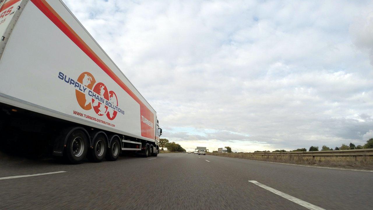 """Ciężarówka z naczepą typu """"plandeka"""" jadąca autostradą."""