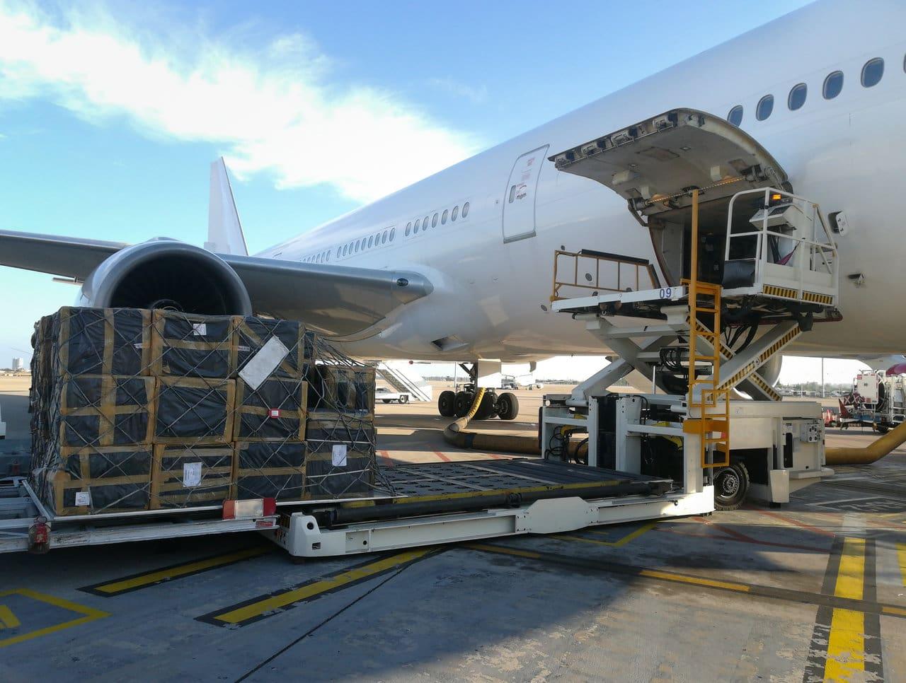 Transport otniczy pandemia. Ładunek w trakcie pakowania do luku bagażowego samolotu pasażerskiego.