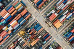 Transport drogowy z Chin. Kontenery składowane w hubie logistycznym, czekające na załadunek i dalszy transport.